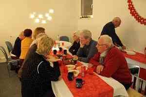 Gäste der Weihnachtsfeier sitzen gemeinsam am Tisch