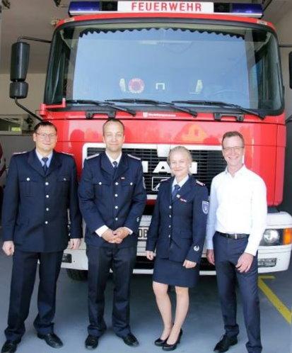 Herr Stamer steht mit Kameradinnen und Kameraden der Freiwilligen Feuerwehr Mönchhagen vor einem Löschfahrzeug.